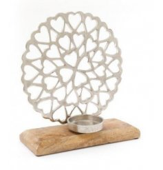 A sleek and simple ornamental heart display on a natural wooden block base with an added tlight holder