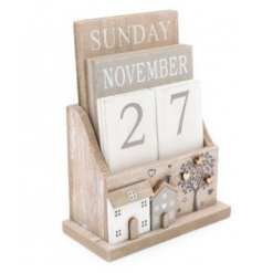 A distressed white toned wooden calendar, set with a house scene and tree to feature on the front