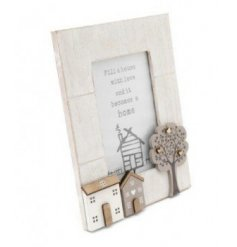 A distressed white toned wooden picture frame, set with a house scene and tree to feature on the front