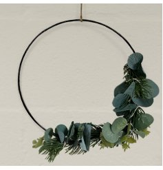 A simple metal hoop wreath entwined with green leaf foliage and added warm glowing LED lights