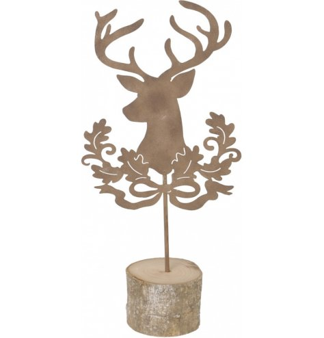 A decorative cut stag and wreath metal decoration placed on a wood bark base