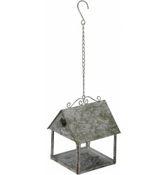 A charmingly rustic inspired metal hanging bird house with a simple heart window