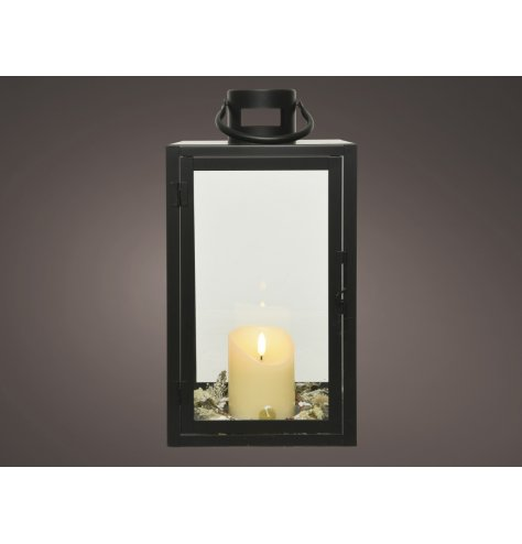 A black framed metal lantern featuring a central placed flameless LED candle and added foliage finish