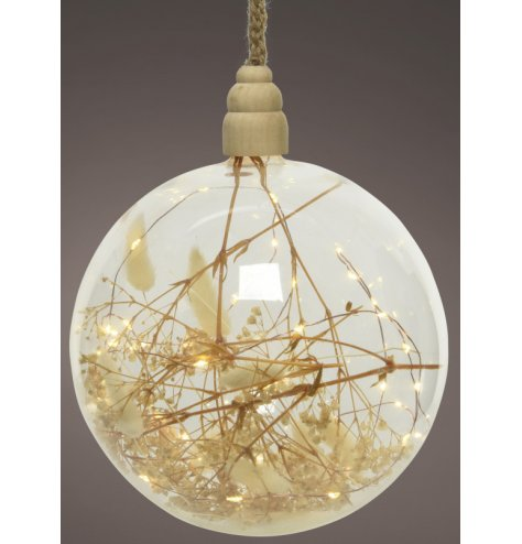A sleek looking clear glass bauble hanger set with warm led lights and dried grass within it