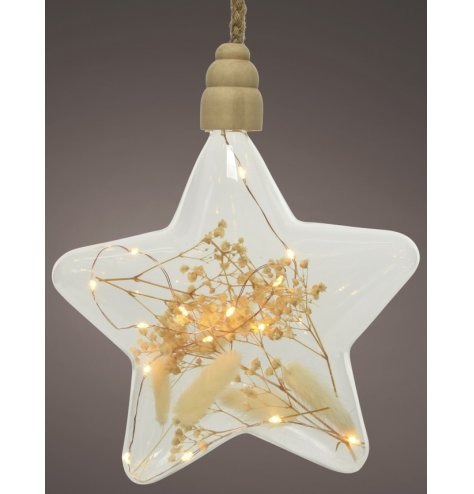 A sleek looking clear glass star hanger set with warm led lights and dried grass within it