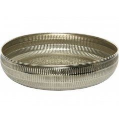 A distressed silver toned decorative bowl with a hammered embossment to surround it