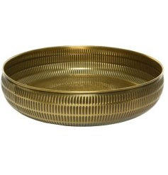 A distressed golden toned decorative bowl with a hammered embossment to surround it