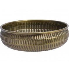 A large metal bowl with a tarnished gold tone and hammered edging