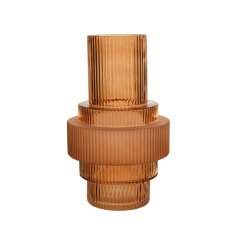 A gorgeously designed glass vase featuring a ridged effect, stacked design and sleek soft orange hue to complete its loo