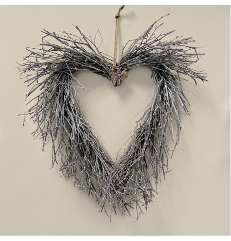 A natural birch heart shaped wreath with an array of real twigs, each set with a subtle white wash