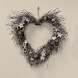 A natural birch heart shaped wreath with a glitter effect and wooden stars.