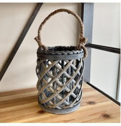 A tall rounded lantern featuring a lattice willow decal and chunky rope handle