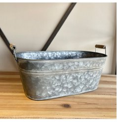 An aged looking metal planter featuring a washed look and wooden handles for feature