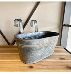 An aged looking metal planter featuring a curved handle, perfect for hanging on fences and balconies