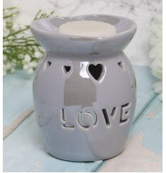 A charmingly simple white toned ceramic oil burner featuring a heart cut decal and bold LOVE finish