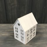 An overly rustic inspired metal house shaped T-light holder