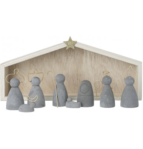 A set of cement based nativity scene figures complete with a natural wood stable behind them