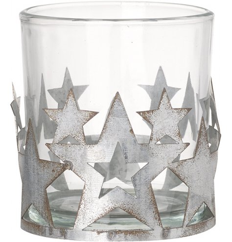 A glass candle pot featuring a metal star cut surround with distressed features