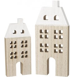 An assorted sized set of natural wooden house decorations with glittery touches and snowy white roofs