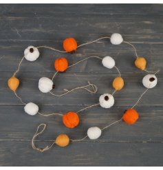 A simple string garland covered with an array of orange and white toned woollen pumpkins