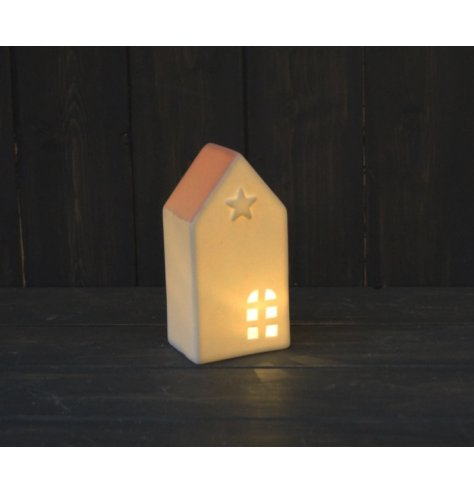 A small ceramic house with white tones and a blush pink roof complete with a warm glowing LED central light and star emb