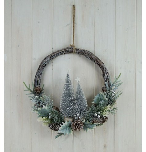 A half done wreath with a woven rattan base and charming festive themed foliage on the bottom