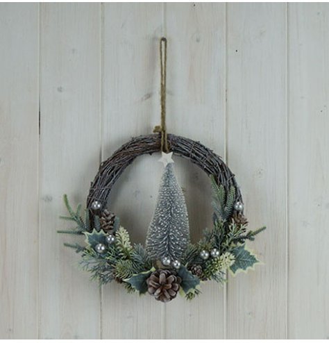 A half done wreath with a woven rattan base and charming festive themed foliage on the bottom.