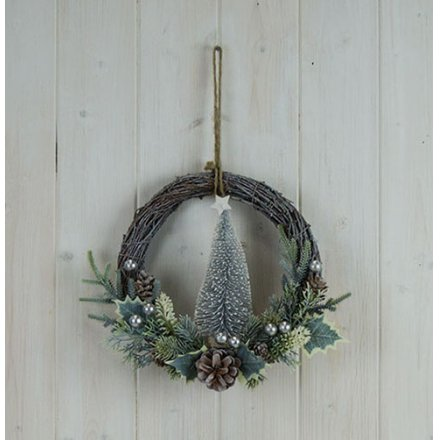 A woven wreath featuring a half done look and added bristle tree centre