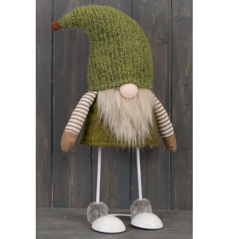 A brown and green toned fabric gonk figure with free standing legs and faux fur trims