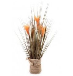 A tall bunch of artificial grass with added autumnal coloured accents and a rope wrapped pot for decal
