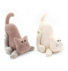 A mix of blush pink and soft cream toned cat doorstops in comical stretched poses