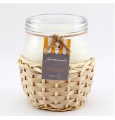 A small candle set within a simplistic inspired woven rattan casing