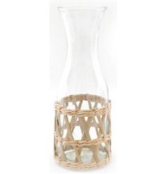 A tall glass carafe set within a simplistic inspired woven rattan casing