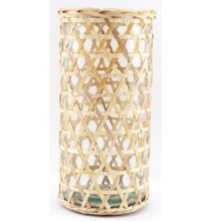 A clear glass vase set within a simplistic inspired woven rattan casing