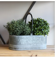 A simplistically decorated metal trough with a zinc look and washed effect and wooden handles