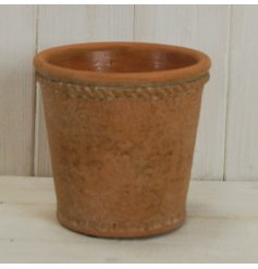 A cement based pot featuring a tapered decal and terracotta toning