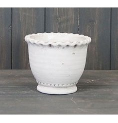 A cement based pot featuring a scalloped edging and white toning