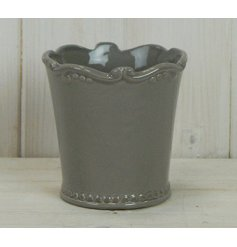 A small ceramic pot featuring a smooth grey glazing and added fleur de lis inspired scalloped edging
