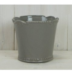 A chic and simple grey toned ceramic pot featuring a fleur de lis inspired scalloped edge