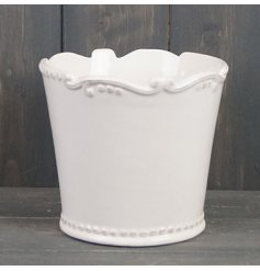A small ceramic pot featuring a smooth white glazing and added fleur de lis inspired scalloped edging