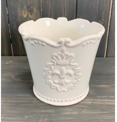 A chic and simple white toned ceramic pot featuring a fleur de lis inspired scalloped edge and motif