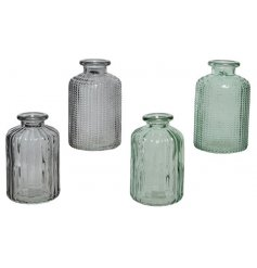 An assortment of 4 blue and green coloured glass bottles, each with a decorative textured surface.