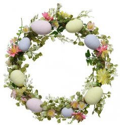 A round wreath, decorated with seasonal grasses, flowers and an added touch of eggs!