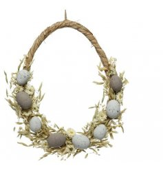 A whimsical egg inspired wreath, decorated with seasonal grasses, flowers and an added touch of eggs!