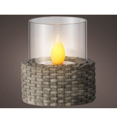 A solar powered flickering flame encased in glass and wrapped in a wicker base.