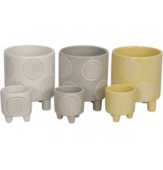 A set of 2 contemporary planters, each with a dot floral design. Complete with small feet.